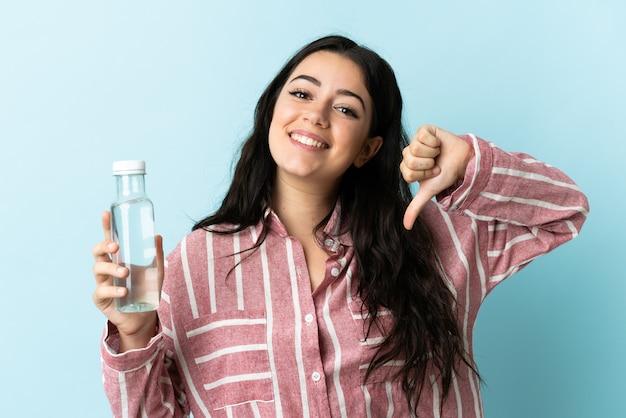 Jovem orgulhosa e satisfeita com uma água isolada na parede azul