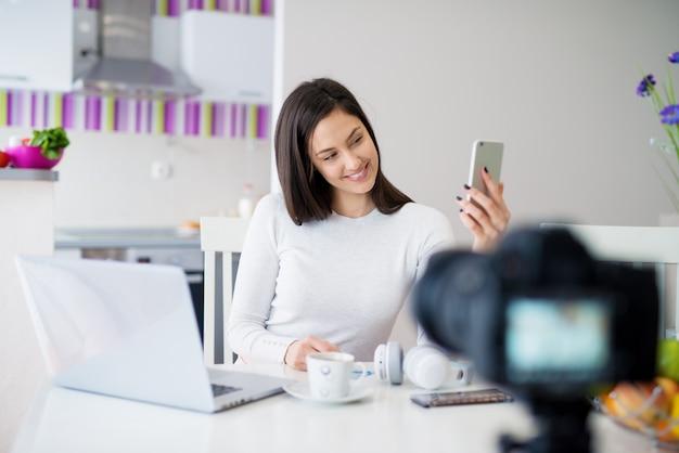 Jovem orgulhosa garota muito alegre está sentada na mesa da cozinha com um laptop e tomando uma selfie enquanto bebe café e sendo tirada foto com a câmera.