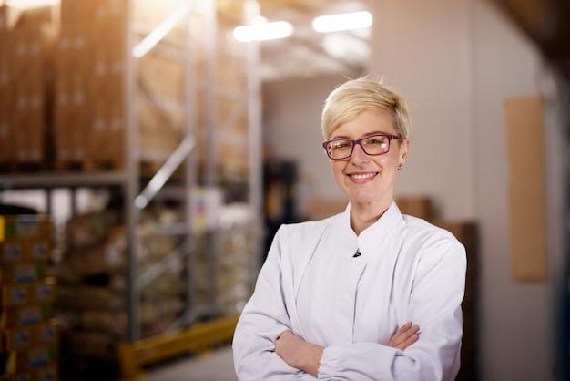 Jovem orgulhosa trabalhadora feliz está segurando os braços cruzados e sorrindo para a câmera na área de armazenamento de carga.