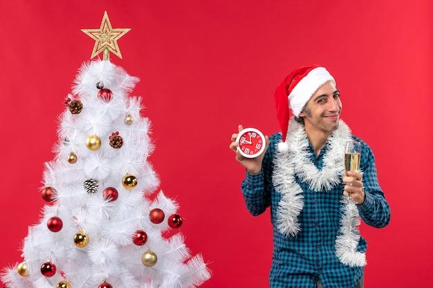 Jovem orgulhoso feliz com chapéu de papai noel, levantando uma taça de vinho e segurando um relógio em pé perto da árvore de natal na foto vermelha