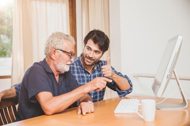 Jovem ou filho ensinando seu pai avô idoso aprendendo a usar o computador em casa.