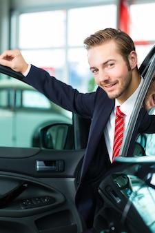 Jovem ou revendedor de automóveis na concessionária de carros