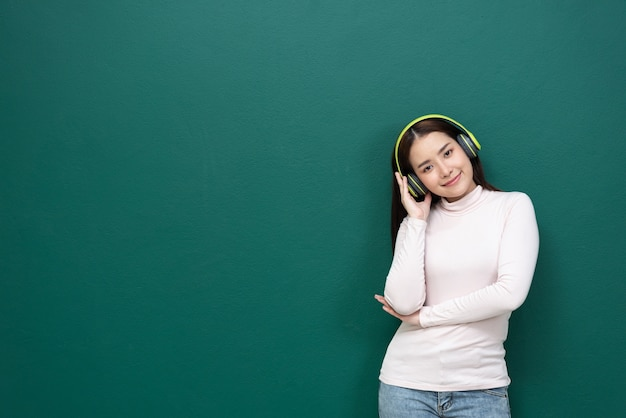 Jovem ouvindo música com fone de ouvido sobre fundo verde
