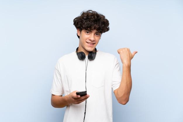 Jovem ouvindo música com um celular sobre parede azul isolada, apontando para o lado para apresentar um produto