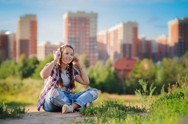 Jovem ouvindo música em fones de ouvido, estilo urbano de rua, estilo de rua ao ar livre