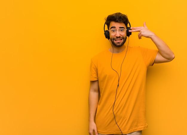 Jovem, ouvindo música, fazendo um gesto de suicídio