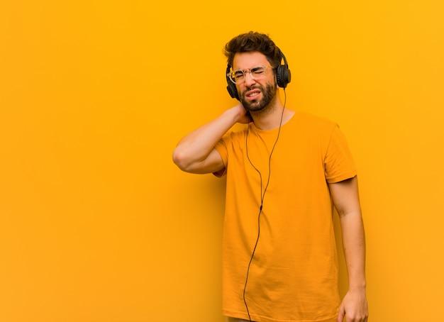 Jovem ouvindo música, sofrendo de dor no pescoço