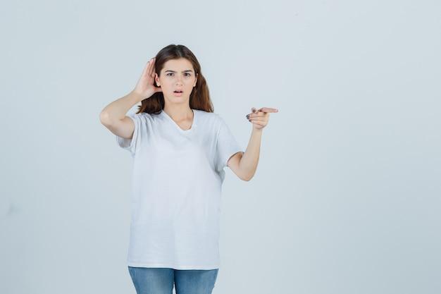 Jovem ouvindo uma conversa privada, apontando para longe em uma camiseta branca e parecendo surpresa. vista frontal.