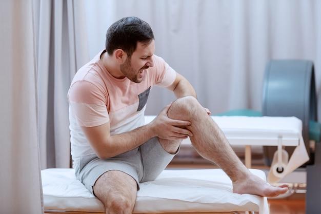 Jovem paciente do sexo masculino caucasiano com dor, sentado na cama de hospital e segurando a perna.