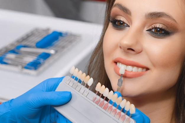 Jovem paciente seleciona a cor do dente