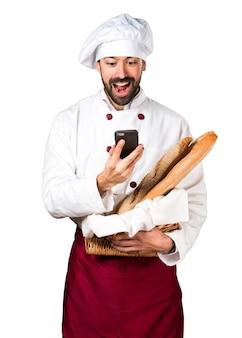 Jovem padaria segurando pão e conversando com o celular