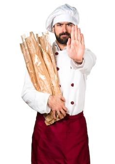 Jovem padaria segurando pão e fazendo sinal de parada