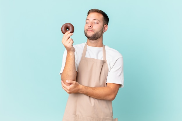 Jovem padeiro bonito com um donut