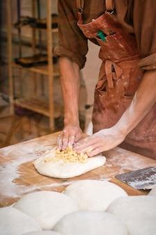 Jovem padeiro preparando massa para fazer pão