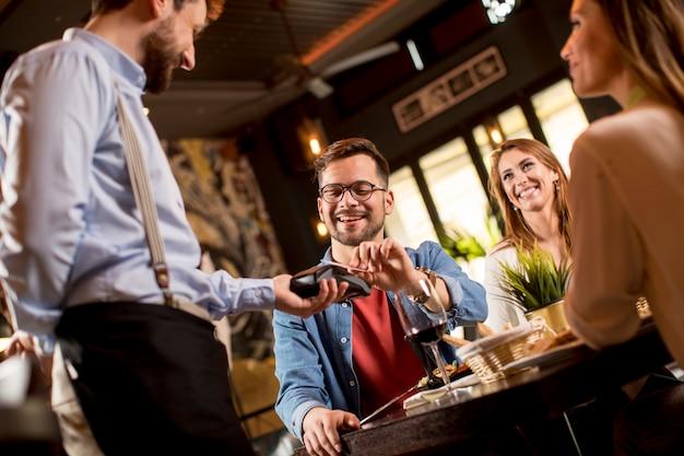 Jovem pagando com cartão de crédito sem contato no restaurante após o jantar