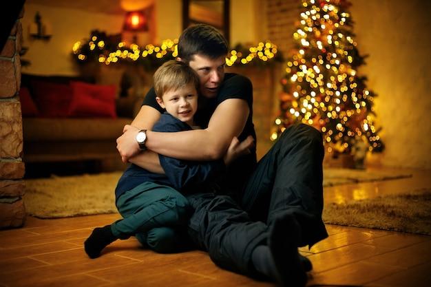 Jovem pai abraça o filho na véspera de ano novo no contexto de uma árvore de natal