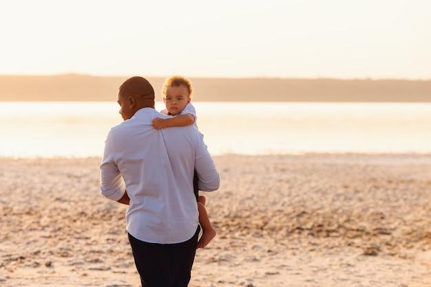 Jovem pai afro-americano caminhando na praia com seu filho pequeno