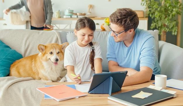 Jovem pai ajudando sua linda filha colegial com pesquisas