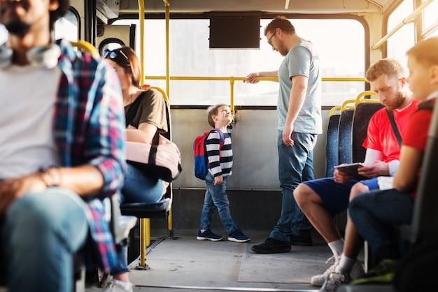 Jovem pai alto e seu filho pequeno estão de pé na extremidade traseira do ônibus e olhando um para o outro.