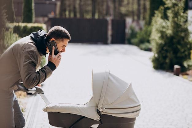 Jovem pai andando com carrinho de bebê no parque