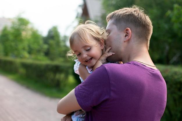 Jovem pai beijando sua filhinha bonita ao ar livre em dia de verão