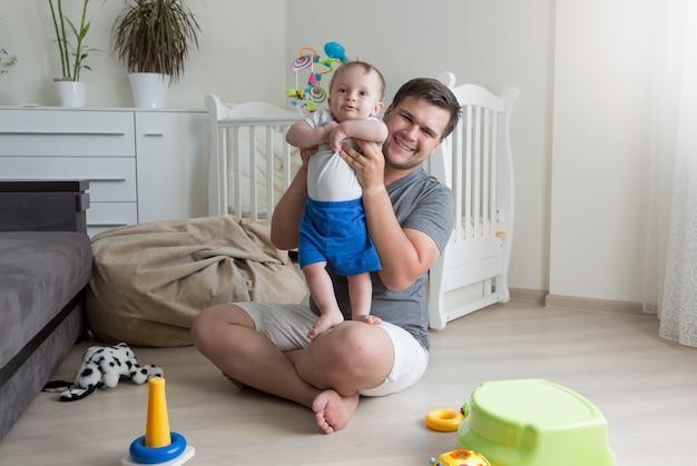 Jovem pai brincando com seu bebê na sala de estar