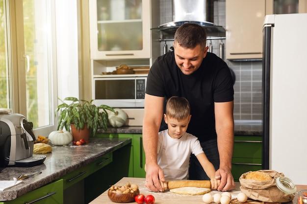Jovem pai carinhoso ajuda filho pequeno em idade pré-escolar a preparar biscoitos