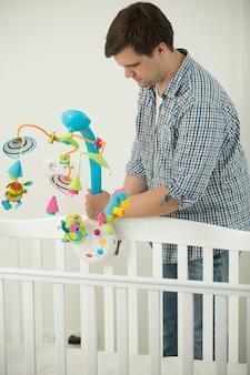 Jovem pai carinhoso montando o berço do bebê e colocando nele um carrossel de brinquedos