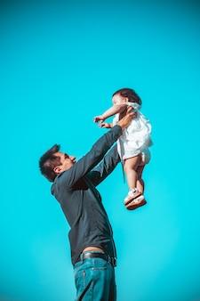Jovem pai com a filha brincando em um parque ao ar livre