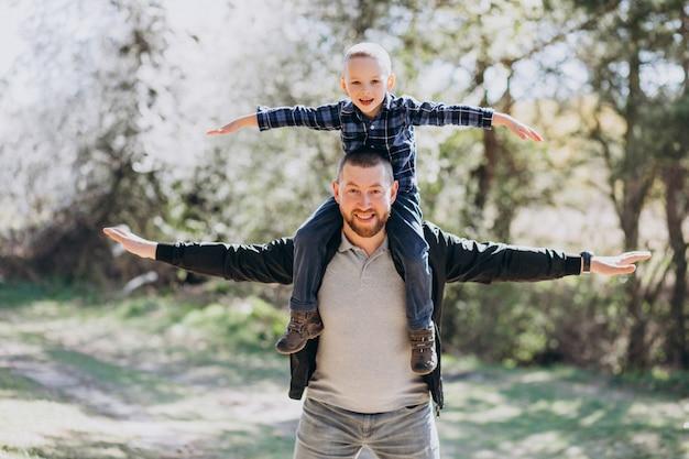 Jovem pai com filho pequeno na floresta