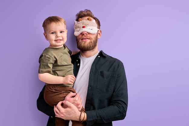 Jovem pai com máscara nos olhos para dormir não quer levar a criança ao jardim de infância pela manhã