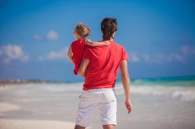 Jovem pai com menina olha para o mar