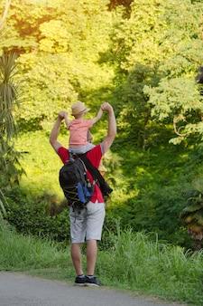 Jovem pai com o filho nos ombros em pé em uma floresta verde tropical.