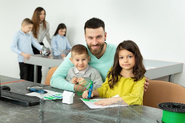 Jovem pai com seu filho e sua filha desenham um desenho usando uma caneta 3d nas aulas de robótica