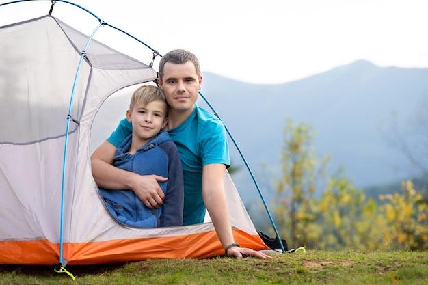 Jovem pai com seu filho filho descansando juntos em uma barraca de acampamento nas montanhas de verão.
