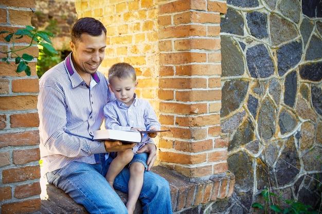 Jovem pai com um filho feliz lendo a bíblia sobre a natureza