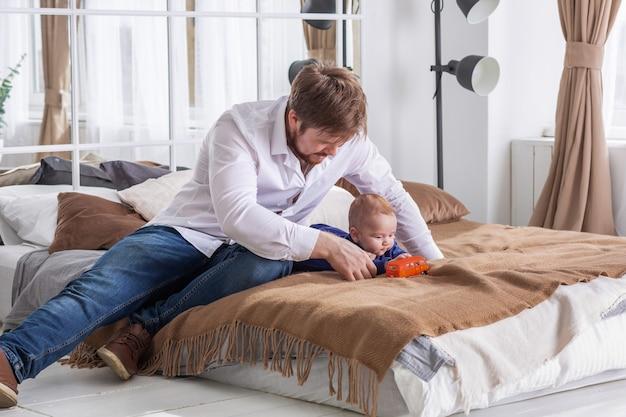 Jovem pai de camisa branca sentado no sofá ao lado de seu filho brincando com o carro pequeno