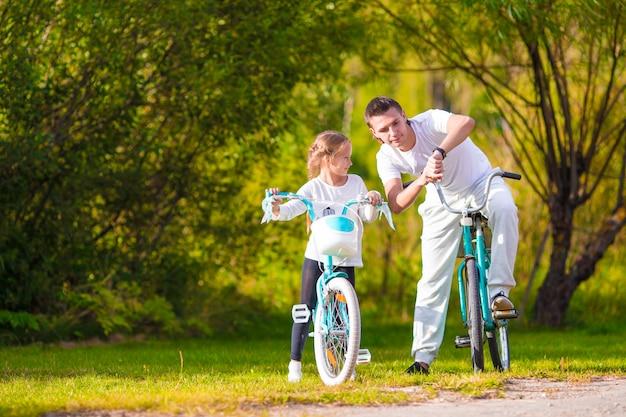 Jovem pai e filha andando de bicicleta no dia quente de verão