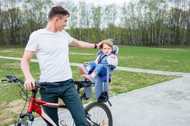 Jovem pai e filha andando de bicicleta no parque.