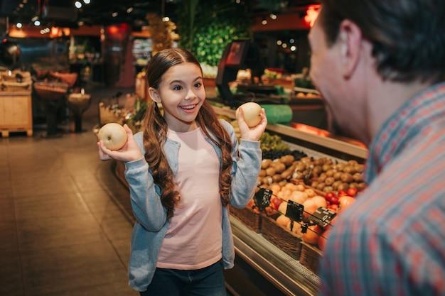 Jovem pai e filha na mercearia. filha alegre olha pai com sorriso. ela segura frutas exóticas nas mãos. homem olha para ela.