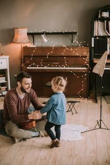 Jovem pai e filha tocando violão no quarto em casa