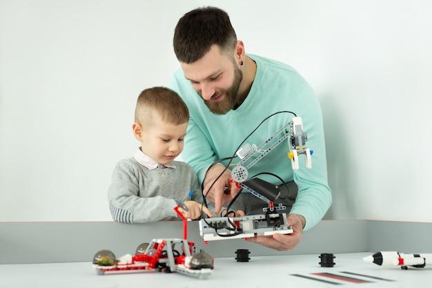 Jovem pai e filho criam um robô em um clube de robótica.