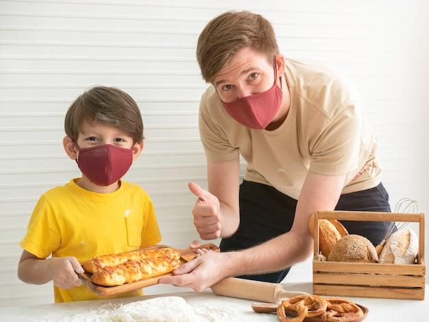 Jovem pai e filho vestindo máscaras enquanto assava pão em casa