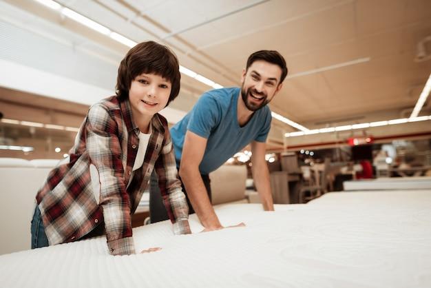 Jovem pai e menino bonitinho escolhendo o colchão
