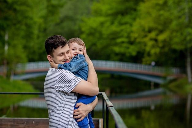 Jovem pai e seu filho sorridente no parque, abraçando e curtindo o tempo juntos, celebração do dia dos pais.