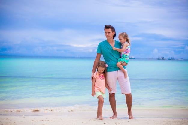 Jovem pai e seus dois filhinhos andando à beira-mar