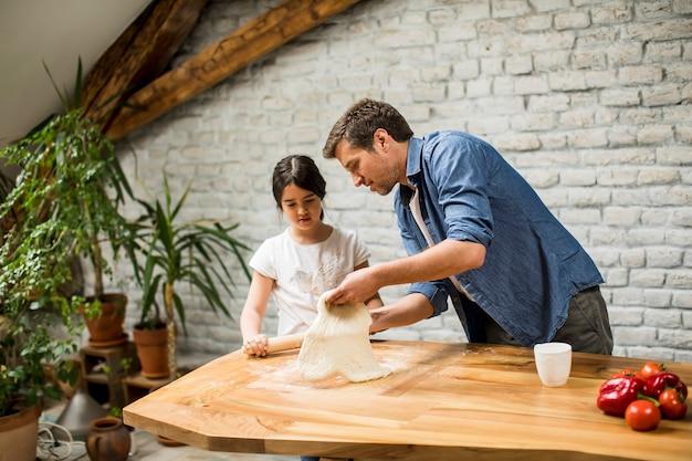 Jovem pai e sua filha fofa fazendo massa em casa cozinha