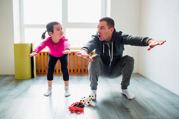 Jovem pai e sua filha pequena estão fazendo exercícios de agachamento exercícios em casa. papai e criança fofa estão treinando em uma esteira coberta perto da janela no quarto dela