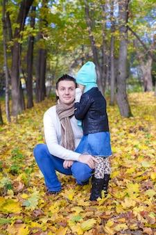 Jovem pai e sua filhinha bonitinha sussurrando no parque outono