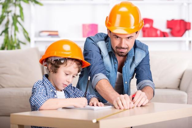 Jovem pai ensina seu filho pequeno mexer.